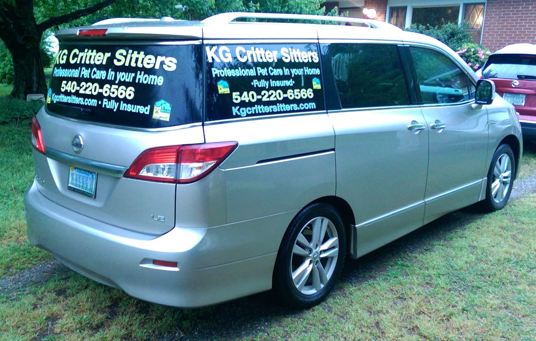 Silver 2011 Nissan Quest with KG Critter Sitters decals on the rear windows.